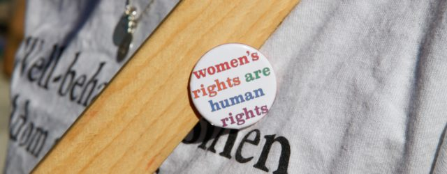 Demonstrantin mit Women's rights are human rights - Button
